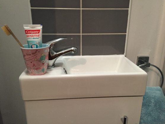 A very small sink with a regular-sized toothbrush holder
